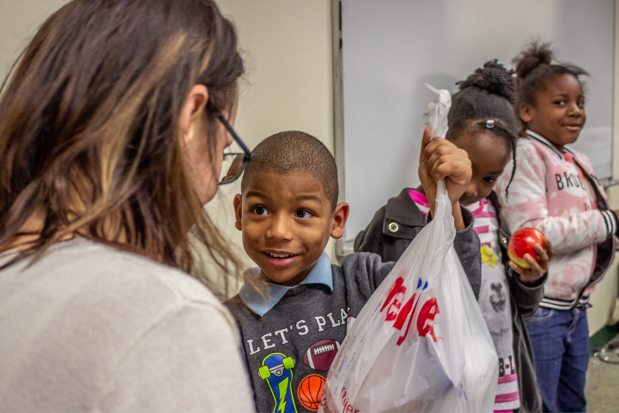Photo of boy holding up his bag of food
